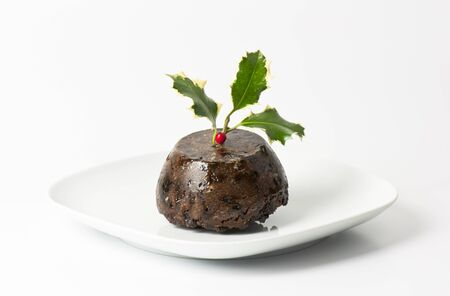 Traditional english Christmas pudding with holly leaves photo