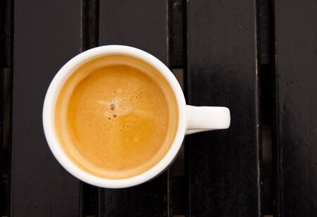 expresso: An espresso in a white cup on a dark wood table Stock Photo