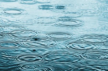 gotas de agua: Gotas de lluvia sobre la superficie del agua Foto de archivo