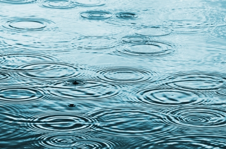 is raining: Rain drops on the water surface Stock Photo