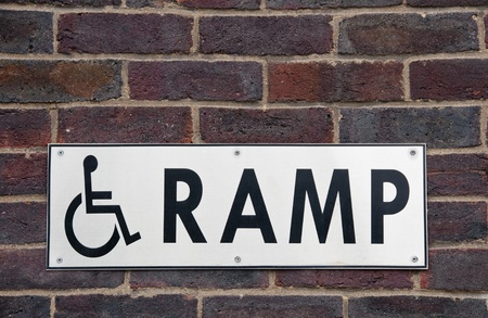 on ramp: Wheelchair ramp sign on a brick wall