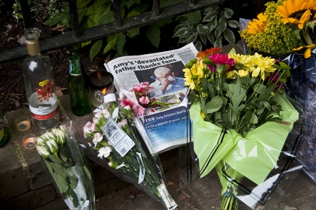 LONDON - JULY 27: Her fans pay tribute to Amy Winehouse in front of her house on Camden square, on July 27, 2011 in London. Amy Winehouse died aged 27 on Saturday, July 23.