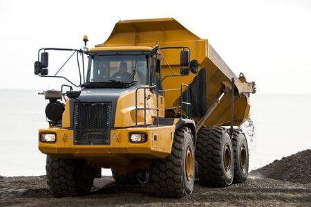 A yellow dump truck unloading gravels photo