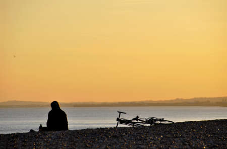 A sitting man and his bicycle on a pebble beach at sunset photo