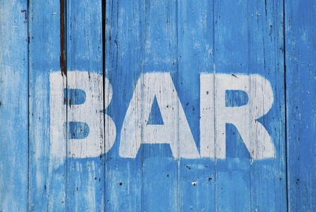 decrepitude: White bar sign painted on a dilapidated blue wooden wall