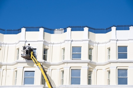 A man cleaning sash windows from outside in the UK photo