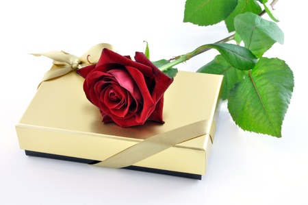 A red rose on a golden gift box photo