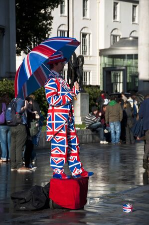 british weather: Human statue dressed in the Union Jack flag, London, UK Editorial
