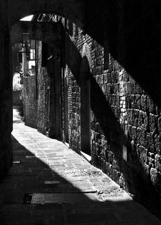 backstreet: Narrow street in San Gimignano, Italy, black and white photography Stock Photo