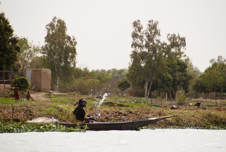 bamako: Bamako, Mali - February 15, 2012: Bozo woman scooping water out of a canoe on the river Niger outside Bamako, Mali