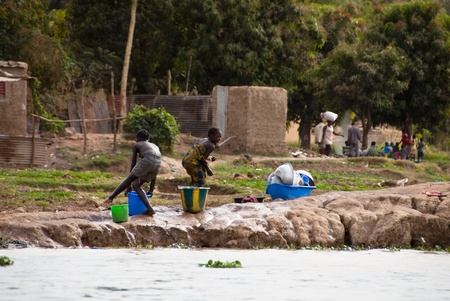 bamako: Bamako, Mali - February 15, 2012: Two children playing with water next to the river Niger in Mali