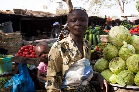 Bamako, Mali - 15 februari 2012: Jonge moeder met haar dochter de verkoop van groenten op een markt in Bamako