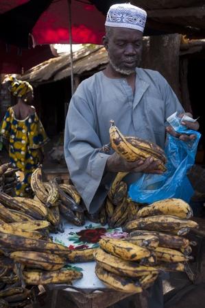 bamako: Bamako, Mali - February 15, 2012: Shopkeeper selling plantain at the local market in Bamako