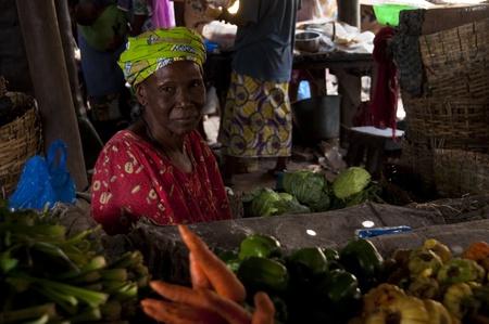 bamako: Bamako, Mali - February 15, 2012: Shopkeeper selling vegetables at the local market in Bamako