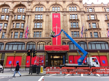 harrods: LONDON, UK, Tuesday 15, 2012. In the early morning workers put the last touch to the special Queens Diamond Jubilee decoration on Harrods facade. Editorial