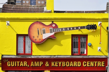 Fake Gibson Les Paul on the facade of the Guitar, Amp & Keyboard Centre in Brighton, England, UK