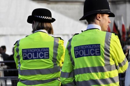Een politie-vrouw en een politieagent het dragen van zichtbaarheid jas
