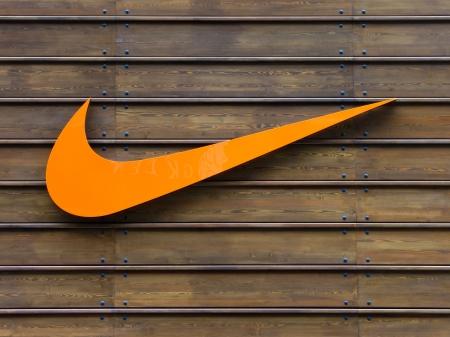 Oranje Nike logo op een houten wand Redactioneel