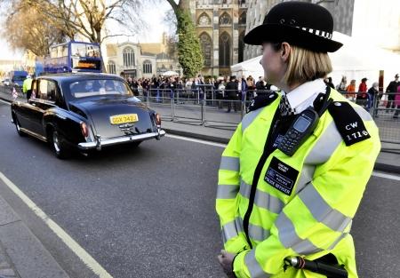 LONDEN, Verenigd Koninkrijk - MAART 12: Een politie vrouw buiten Westminster Abbey, waar koningin Elizabeth II neemt deel aan de Commonwealth Day ceremonie op 12 maart 2012 in Londen, Verenigd Koninkrijk.