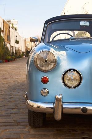 Blauwe vintage auto geparkeerd in een geplaveide straat Stockfoto