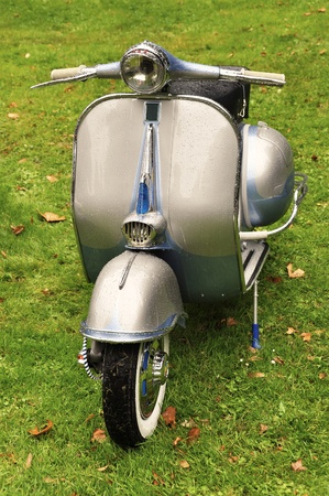 old motorcycle: Vintage scooter on the lawn after the rain