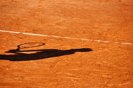 Tennis player shadow on a clay tennis court photo