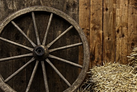 Vintage wooden carriage wheel, straw and wood background photo