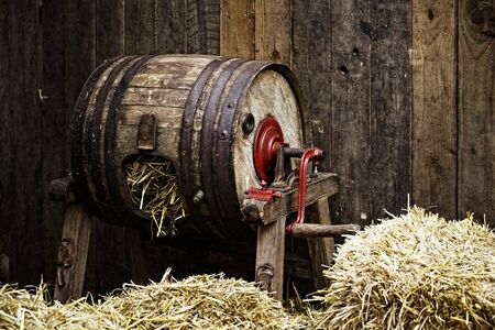 Vintage barrel-type butter churn filled with straw, wooden background Stock Photo - 17543258
