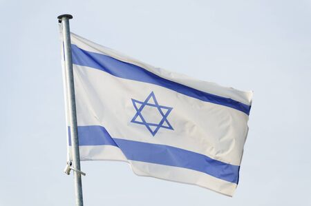 israeli: Israeli flag on a mast, sky background Stock Photo