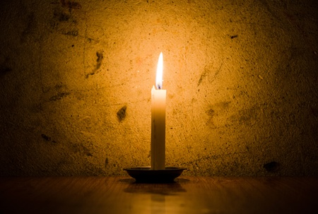 A candle burning, grungy wall background and vignette