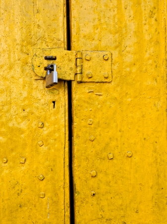 Padlock on an old yellow metallic door photo