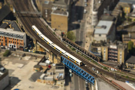 tilt: Aerial view of a train on a bridge in London, tilt-shift effect, England, UK