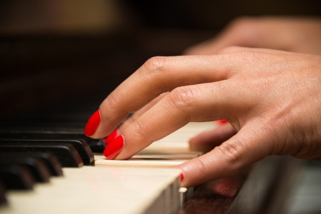 Female pianist hands closeup and piano keyboard photo