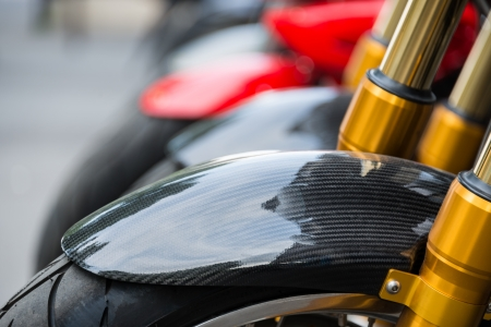 Motorbike detail, carbon fiber mud guard and golden dampers Stock Photo