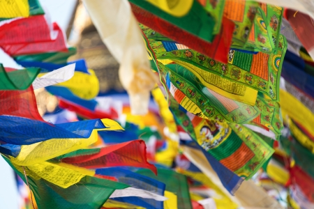 buddhism prayer belief: Prayer flags flying in the wind at Bodhnath stupa in Kathmandu, Nepal Editorial