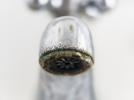 limestone: Old and grungy tap closeup, white background Stock Photo