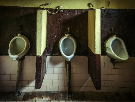 gents: Three dirty urinals in public gents Stock Photo