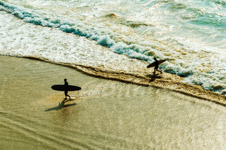 Two surfers going back to the beach photo