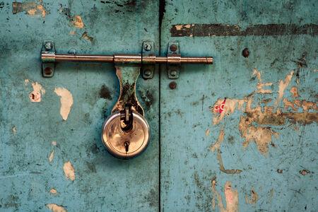 padlocked: Padlock on a turquoise grungy door Stock Photo