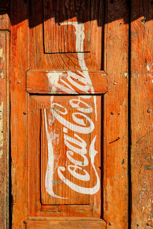 KATHMANDU, NEPAL - CIRCA JANUARY 2014  Vintage Coca-Cola adverisement painted on a red wooden door