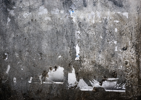 Grungy concrete wall with torn posters photo