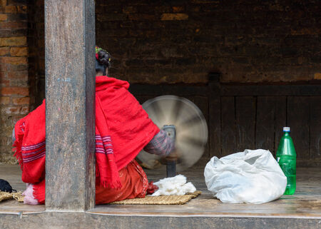 Nepalese woman spinning wool in Bhaktapur photo