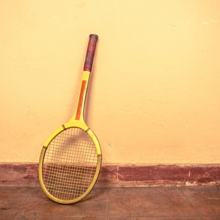 Vintage tennis racket against a wall photo