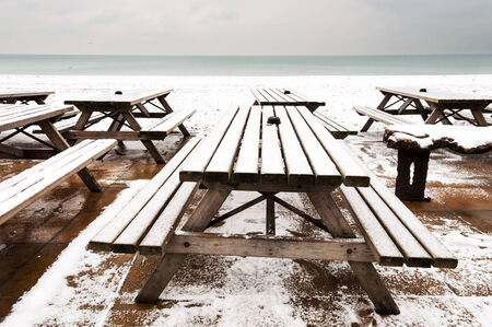 deserted: Wooden tables covered by snow in Brighton, UK Stock Photo
