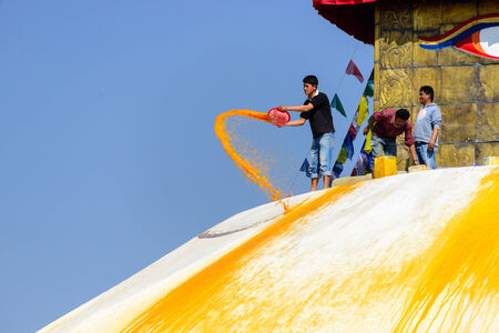 bodnath: KATHMANDU, NEPAL - JANUARY 27, 2014  A man throws orange paint on Boudhanath Stupa as part of the renovation and painting work which will cost four million Nepalese Rupees