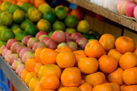 Oranges and other fruits on display on a market stand