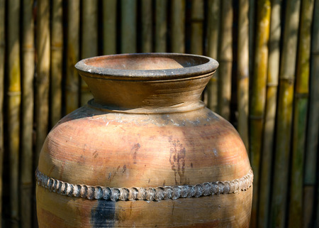 Big jar in a garden, bamboo wall background photo