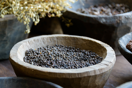 ayurvedic: Black pepper in a wooden bowl and other spices and herbs used in ayurvedic medicine