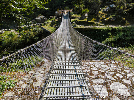 Suspension bridge over a river in Nepal photo