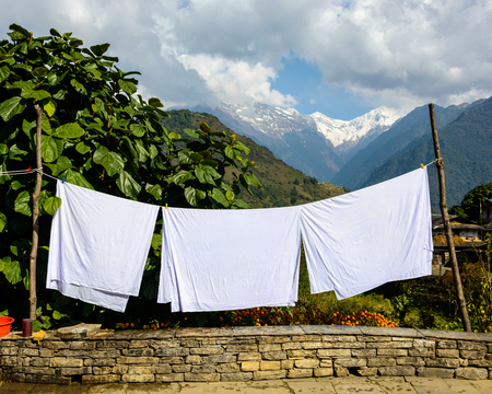 bedsheets: Three white sheets drying in the sun in Ghanfruk, Nepal